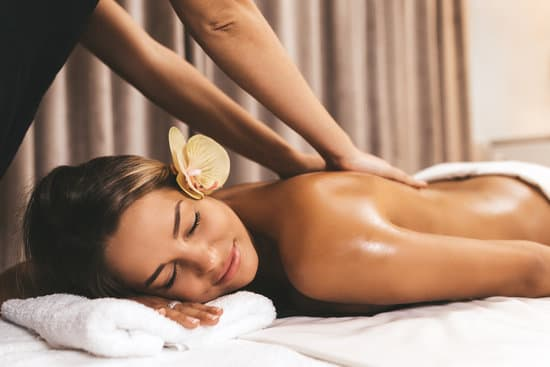 Beautiful young woman relaxing with hand massage at beauty spa